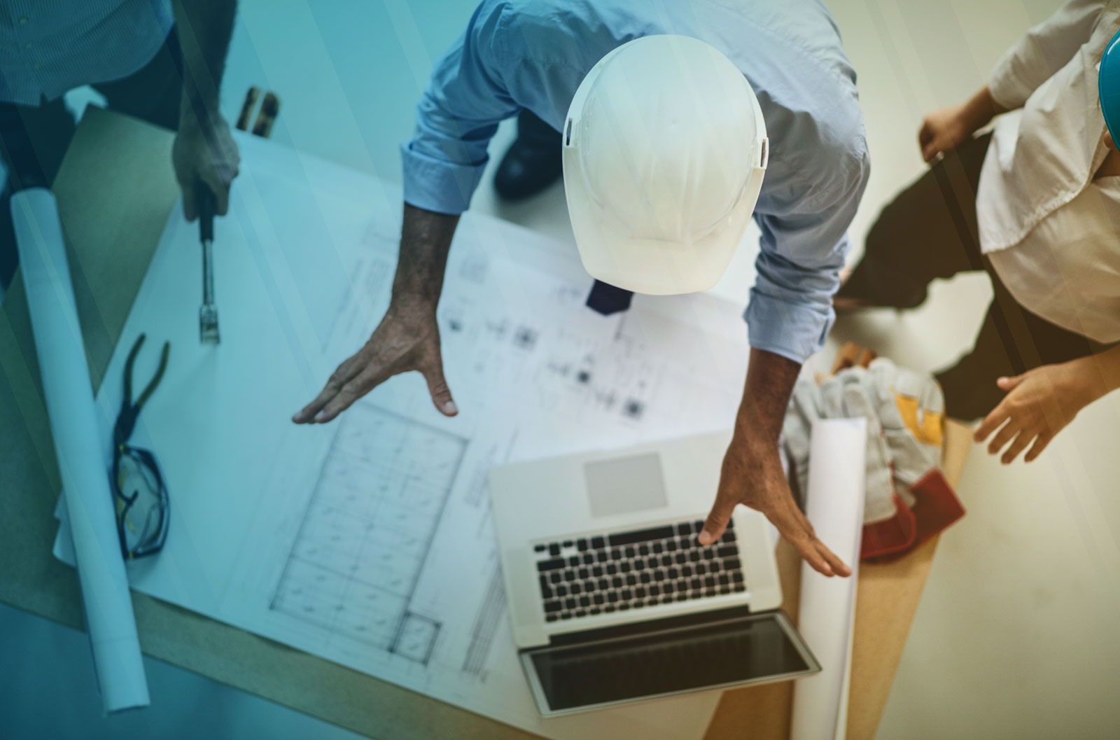 Construction Site Supervisor coordinating with team members over blueprints